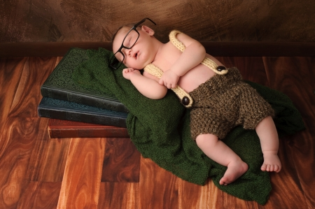 Ten day old newborn baby boy wearing crocheted shorts and suspenders  He has on adult reading glasses and is sleeping on a stack of vintage books