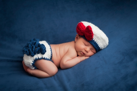 Eight day old newborn baby girl wearing a white and blue sailor costume  She is sleeping contentedly on her stomach  Shot in the studio on navy blue velvet