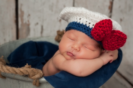 Eight day old newborn baby girl wearing a white and blue sailor hat with red bow  She is sleeping inside of a galvanized bucket with burlap handles  Shot in the studio on a rustic whitewashed wood backdrop
