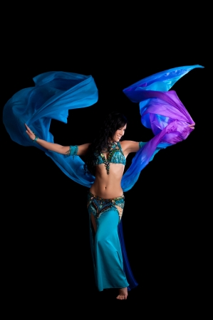 An exotic belly dancer wearing a teal and royal blue costume  She is dancing with a flowing blue and purple silk veil  Shot in the studio on a black background