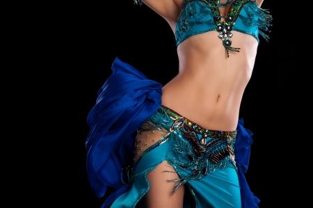 buikdansen: Torso van een vrouwelijke buik danseres dragen van een blauwgroen blauw kostuum en schudt haar heupen geïsoleerd op een zwarte achtergrond