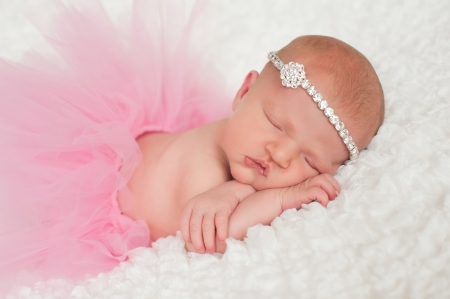 Sleeping 8 day old newborn baby girl wearing a pink tutu and rhinestone headband  She is sleeping on her tummy on a white billowy blanket  Stock Photo