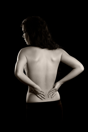 lower back: A woman holding her lower back as if experiencing pain   Stock Photo