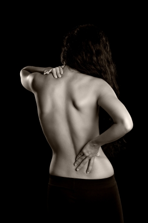 woman back: A young woman holding her lower back and shoulder as if experiencing pain