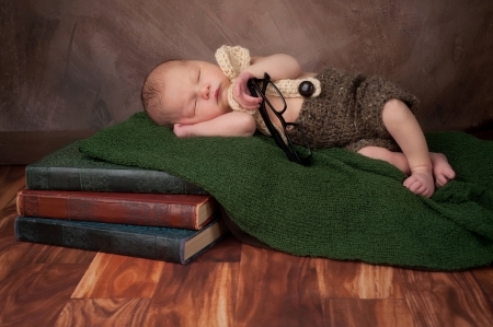 Five day old newborn baby boy wearing crocheted shorts a bow tie and suspenders  He is holding adult reading glasses and sleeping on a stack of vintage books  photo