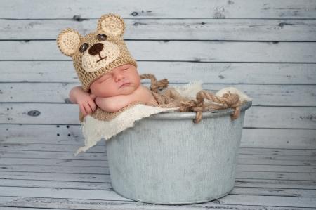 teddy bear: Cinco d�as de edad beb� reci�n nacido que llevaba un sombrero de ganchillo oso de peluche marr�n y dormir en un cubo galvanizado Filmada en el estudio sobre un fondo de madera blanqueada