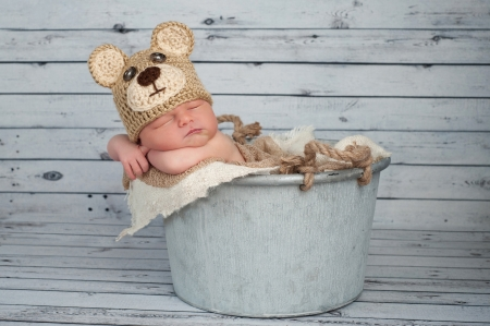 Five day old newborn baby boy wearing a brown crocheted Teddy Bear hat and sleeping in a galvanized bucket  Shot in the studio on a bleached wood background