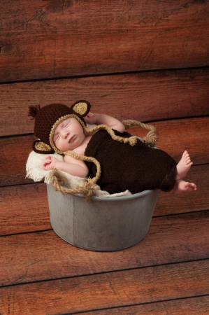 A newborn baby wearing a crocheted monkey costume and sleeping in a galvanized bucket  Shot in the studio with a rustic wood background  photo