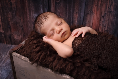 sheepskin: 9 day old newborn baby boy sleeping on his back in an old vintage wood crate  Shot in the studio on a rustic, barn wood background