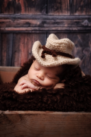 9 day old newborn baby boy wearing a crocheted cowbow hat and sleeping on his stomach in a wooden crate  Shot in the studio on a rustic, barn wood background