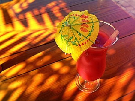 A Rum Runner Cocktail on a Wooden Table with Tropical Palm Tree Shadows 写真素材
