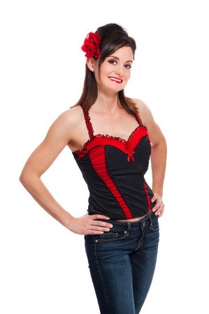 A beautiful Rockabilly girl wearing a black and red bustier top, jeans, and a red flower hair accessory  Shot in the studio and isolated on a white background