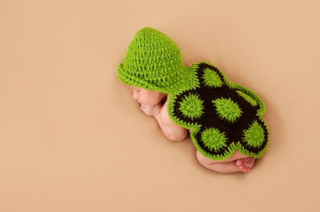 A sleeping newborn baby wearing a crocheted turtle costume  Shot in the studio on a beige blanket  Archivio Fotografico