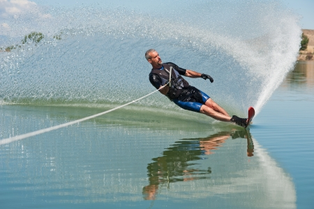 A 50 yr  old man slalom waterskiing on Sweitzer Lake in Delta, Colorado  He is carving the water with his ski as he makes a turn, creating a  rooster tail  of water