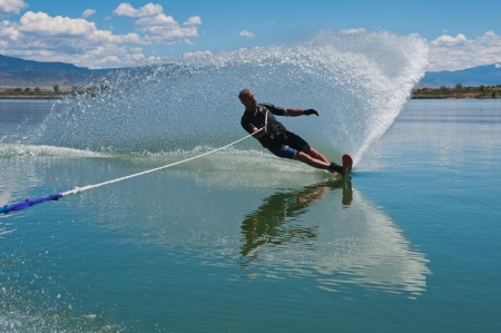 A 50 yr  old man slalom waterskiing on Sweitzer Lake in Delta, Colorado  He is carving the water with his ski as he makes a turn, creating a  rooster tail  of water  photo