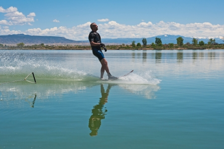 50 55: A 50 yr  old man drops the ski rope, finishing his run of slalom waterskiing on Sweitzer Lake in Delta, Colorado