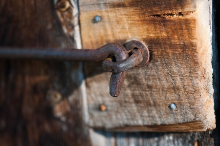 outbuilding: A close-up shot of a closed rusty, antique, hook and eye latch located on the door of an old wooden outbuilding