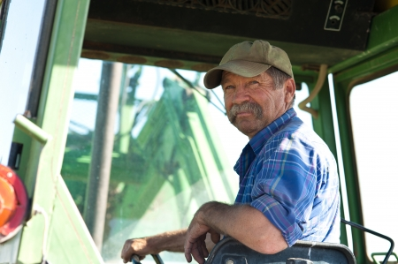 A candid portrait of a senior male farmer sitting in a tractor  photo