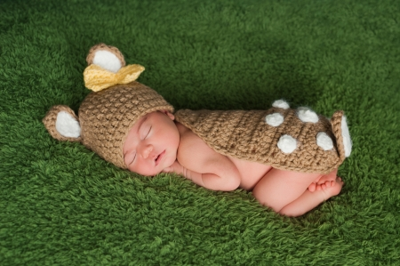 A newborn baby girl wearing a Whitetail deer / fawn costume. She is sleeping on a grass green fuzzy blanket.