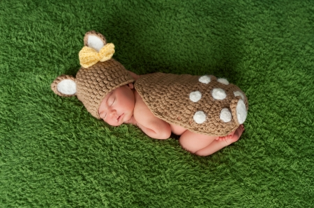 A newborn baby girl wearing a Whitetail deer  fawn costume. She is sleeping on a grass green fuzzy blanket. photo
