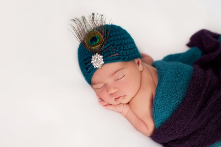A newborn baby girl wearing a teal and purple peacock costume. She is sleeping on her stomach a white blanket.