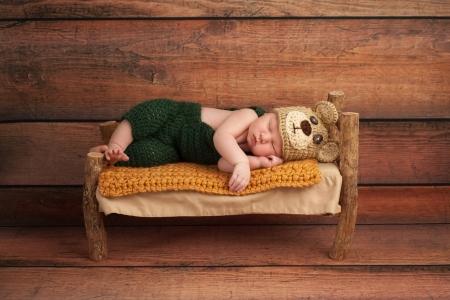 かぎ針編みの緑のオーバー オールおよび無作法な木のスタジオのミニチュア木製ベッド ショットで寝てるクマ帽子身に着けている生まれたばかりの