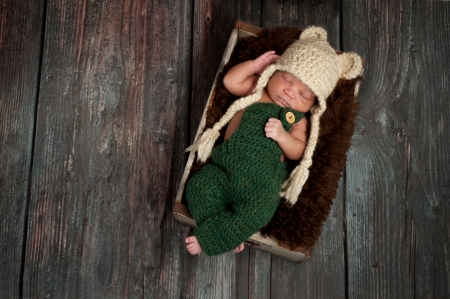 Portrait of a newborn baby boy wearing crocheted green overalls and bear hat  He is sleeping in an old wooden crate  Shot in the studio on a rustic wood