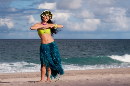 A beautifu, happy hula dancer poses on the beach.