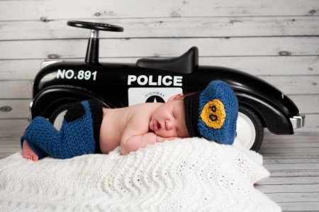 Sleeping two week old newborn baby wearing a police officer costume with a vintage toy police cruiser in the background.
