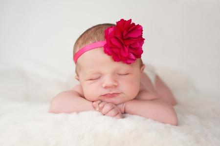 ホットのピンクの花ヘッドバンドを身に着けて美しい新生児の赤ちゃんの肖像画。彼女はクリーム色の羊皮の敷物の上に眠っています。