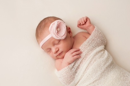 A portrait of a beautiful, 12 day old newborn baby girl wearing a light pink flower headband. She is swaddled and sleeping on her back on a cream colored blanket.