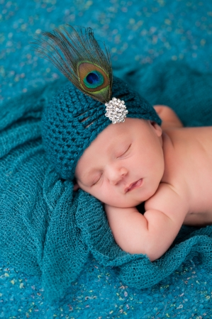 A 12 day old sleeping newborn baby girl wearing an elegant teal flapper hat with rhinestone button and peacock feather.