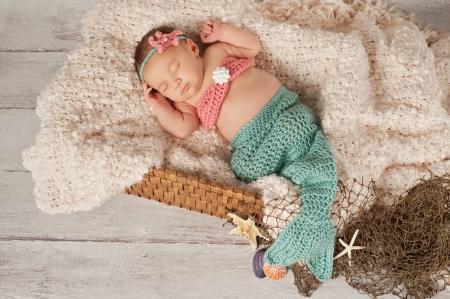 生まれたばかりの赤ちゃん女の子のかぎ針編みティールとサンゴを着て着色人魚姫の衣装。彼女は、漂白された木材の背景とバスケットで寝ていま 写真素材