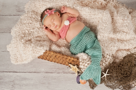 Newborn baby girl wearing a crocheted teal and coral colored mermaid costume. She is sleeping in a basket with a bleached wood background.