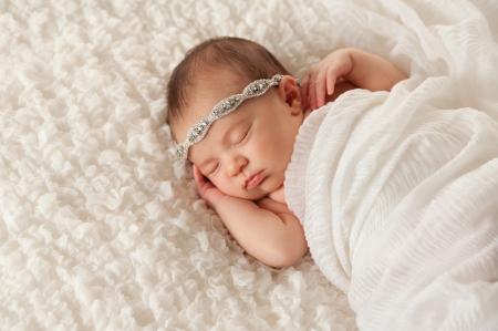 cintillos: A dormir dos semanas de edad recién nacido niña llevaba una diadema rhinestone. Ella está envuelta en tela de gasa blanca y dormir sobre una manta blanca ondeante.