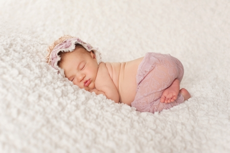 Full length shot of a sleeping two week old newborn baby girl wearing a lacy bonnet and lavender colored pants. She is sleeping on a white billowy blanket. Standard-Bild