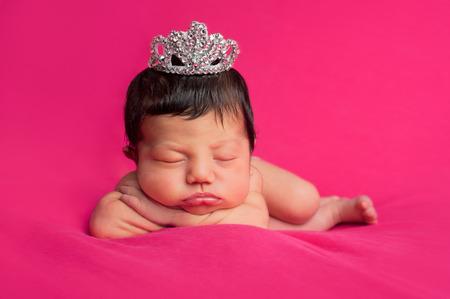 Een mooie 8 dagen oud pasgeboren baby meisje draagt een fancy strass tiara Schot in de studio op een hete roze achtergrond