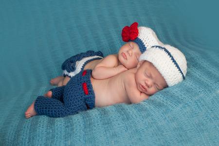 gemelos niÑo y niÑa: Cinco semanas de edad niño dormido y niñas recién nacidos gemelos fraternales que están usando marinero ganchillo equipan Un bebé está acostado sobre su estómago y la otra se apoya en la parte superior de su hermana