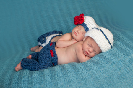 Five week old sleeping boy and girl fraternal twin newborn babies  They are wearing crocheted sailor outfits  One baby is lying on her stomach and the other is propped on top of her sister  photo