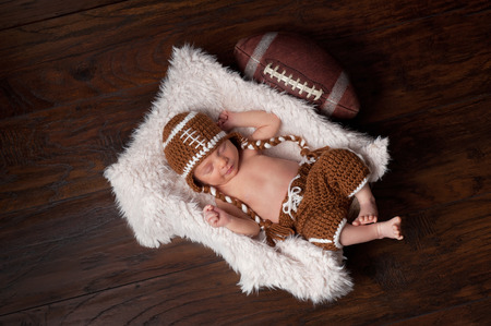 A 12 day old newborn baby boy sleeping in a fur lined crate and wearing a crocheted American football costume
