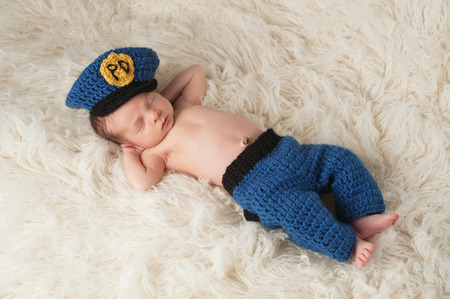 A 12 day old newborn baby boy wearing a crocheted police officer costume He is sleeping on his back with his hands behind his head