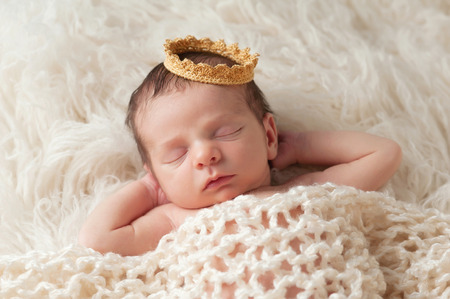 Portrait of a 12 day old newborn baby boy wearing a gold crown  He is sleeping on a beige flokati rug with his hands behind his head
