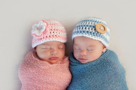 Fem veckor gamla sovande pojke och flicka broderlig tvilling nyfödda De bär virkade rosa och blå randiga mössor Stockfoto