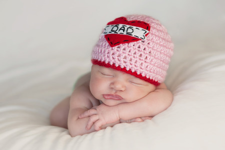 Five week old sleeping baby girl wearing a crocheted  Love Dad  beanie  Cute shot to use for Father