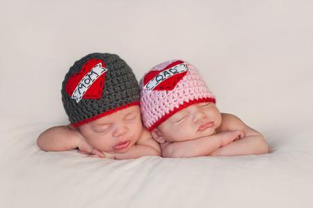 Cinco semanas de edad niño dormido y niñas recién nacidos gemelos fraternales que están usando gorros de ganchillo El amor de la mamá y del papá del amor