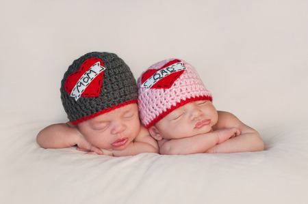 Five week old sleeping boy and girl fraternal twin newborn babies  They are wearing crocheted  Love Mom  and  Love Dad  beanies