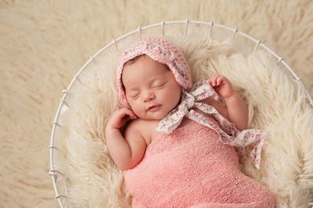 Een portret van een vijf weken oud pasgeboren baby meisje draagt een roze bonnet Ze heeft een subtiele glimlach en is rustig slapen in een mand Stockfoto