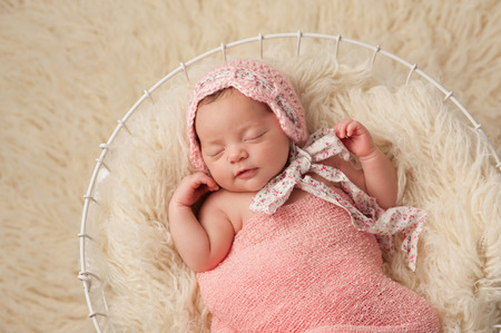 A portrait of a five week old newborn baby girl wearing a pink bonnet  She has a subtle smile and is peacefully sleeping in a wire basket  Standard-Bild