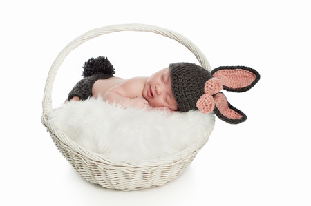 2 month old smiling newborn baby girl wearing a gray and pink costume consisting of bunny ears, bow and a bunny tail diaper cover
