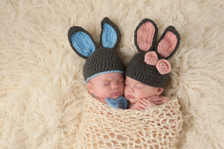 Sleeping 2 month old newborn baby twins wearing bunny costumes. They are swaddled together in a hugging position.